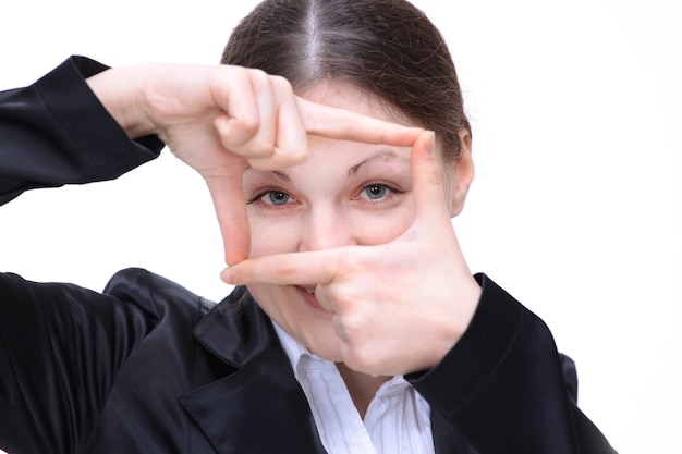 Młoda biznesowa kobieta pokazuje ramkę jego palców w pobliżu jej twarzy. na białym tle.