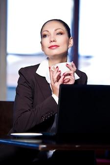 Młoda biznesowa kobieta pozuje na biurowym tle.