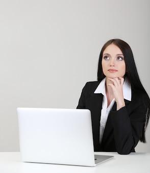 Młoda biznesowa kobieta pracująca z komputerem, na szaro