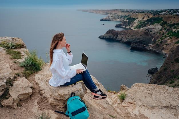 Młoda biznesowa kobieta pracuje na komputerze na plaży na skale