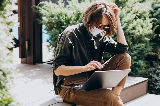Młoda biznesowa kobieta pracuje na komputerze od domu w masce