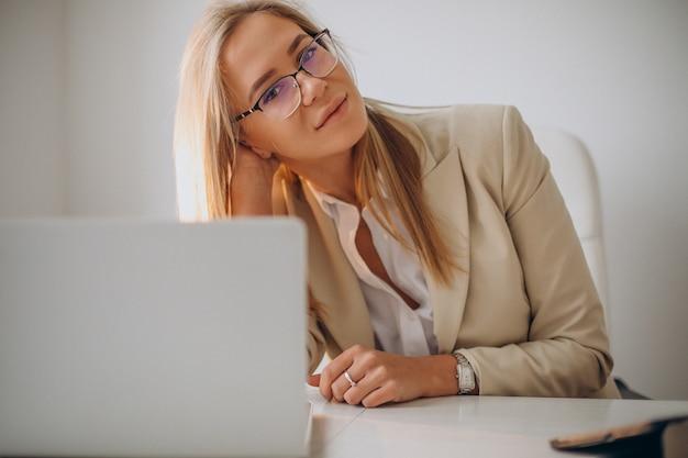 Młoda biznesowa kobieta pracuje na komputerze w biurze