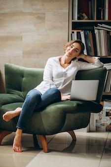 Młoda biznesowa kobieta pracuje na komputerze w domu