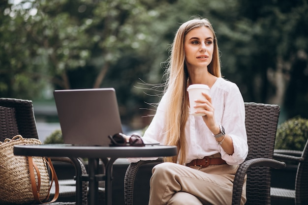Młoda biznesowa kobieta pracuje na laptopie outside w kawiarni
