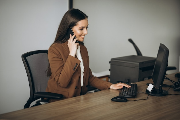 Młoda biznesowa kobieta pracuje na laptopie w biurze