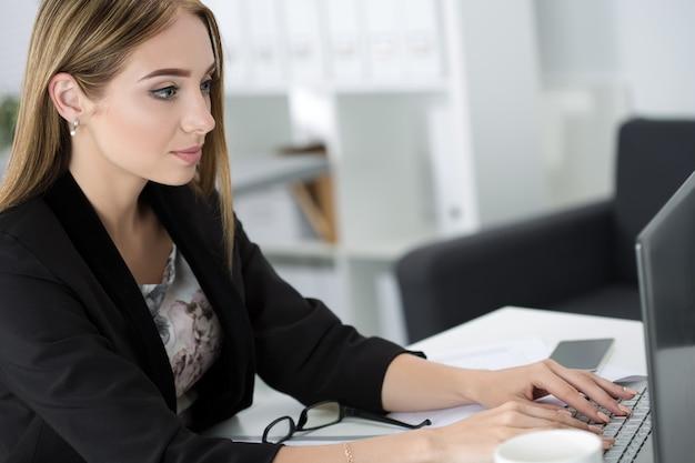 Młoda biznesowa kobieta pracuje na laptopie w biurze.
