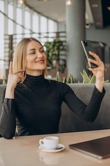 Młoda biznesowa kobieta pracuje na laptopie w kawiarni