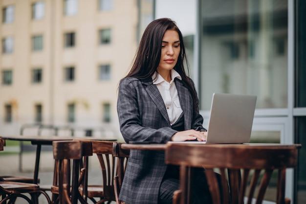 Młoda biznesowa kobieta pracuje na laptopie
