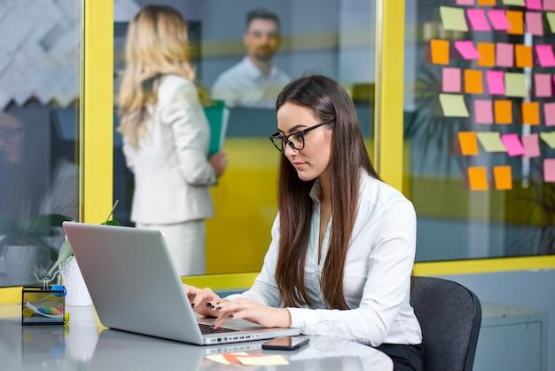 Młoda biznesowa kobieta pracuje na notatniku