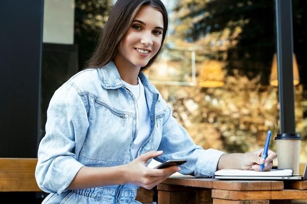 Młoda biznesowa kobieta pracuje na otwartym tarasie w domu, siedząc przed laptopem, trzymając smartfon w dłoni.