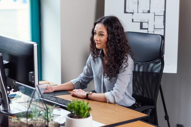 Młoda biznesowa kobieta pracuje przy komputerem w nowożytnym biurze.
