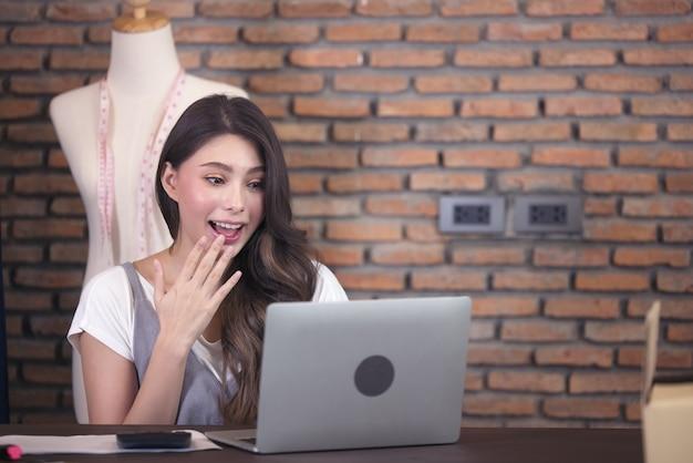 Młoda biznesowa kobieta pracuje w sprzedaży online. niespodzianka i szok na twarzy azjatyckiej kobiety, która odniosła sukces podczas wielkiej sprzedaży swojego sklepu internetowego. zakupy online