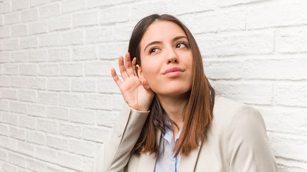 Młoda biznesowa kobieta próbuje słuchać plotki