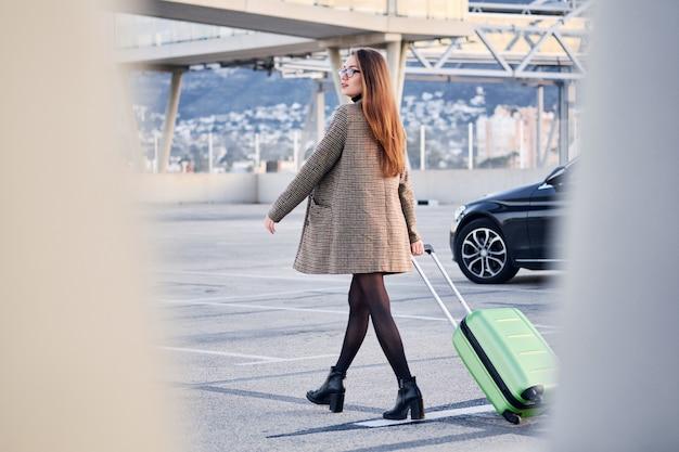 Młoda Biznesowa Kobieta Przeciw Czarnemu Luksusowemu Samochodowi Na Tle. Premium Zdjęcia