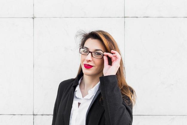 Młoda biznesowa kobieta przystosowywa szkła outside