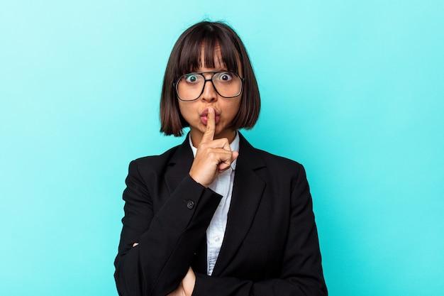 Młoda biznesowa kobieta rasy mieszanej na białym tle na niebieskim tle dochowując tajemnicy lub prosząc o ciszę.