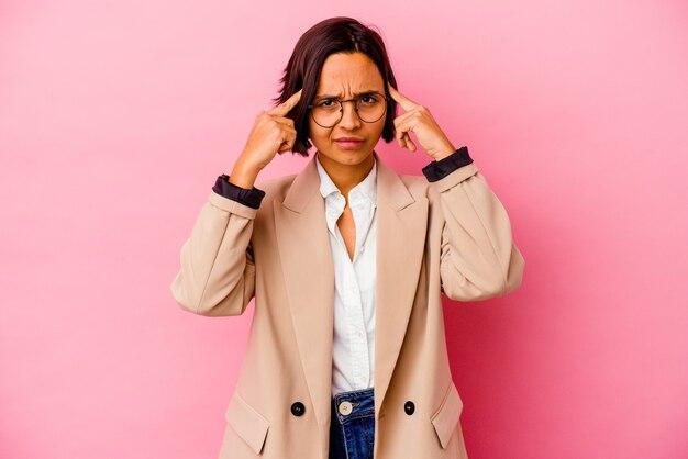 Młoda biznesowa kobieta rasy mieszanej na białym tle na różowej ścianie koncentruje się na zadaniu, trzymając wskazujące głowę palce.