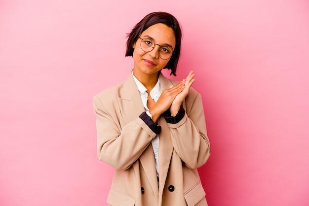 Młoda biznesowa kobieta rasy mieszanej na białym tle na różowym tle czuje się energiczna i wygodna, pocierając ręce pewnie.
