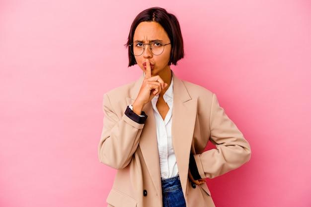 Młoda biznesowa kobieta rasy mieszanej na białym tle na różowym tle dochowując tajemnicy lub prosząc o ciszę.
