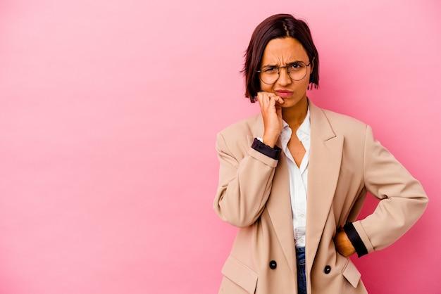 Młoda biznesowa kobieta rasy mieszanej na białym tle na różowym tle, która czuje się smutna i zamyślona, patrząc na miejsce.
