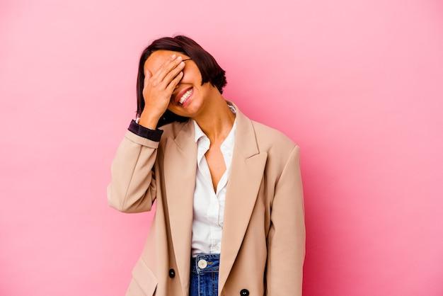 Młoda biznesowa kobieta rasy mieszanej na białym tle na różowym tle śmieje się radośnie trzymając ręce na głowie. koncepcja szczęścia.