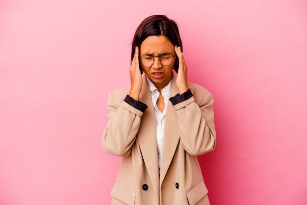 Młoda biznesowa kobieta rasy mieszanej na białym tle na różowym tle zakrywającym uszy palcami, zestresowana i zdesperowana przez głośno otoczenia.