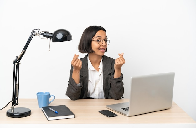 Młoda biznesowa kobieta rasy mieszanej pracująca w biurze gest zarabiania pieniędzy
