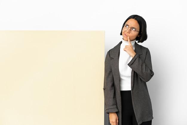 Młoda biznesowa kobieta rasy mieszanej z dużym banerem na białym tle, mająca wątpliwości podczas patrzenia w górę