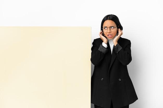 Młoda biznesowa kobieta rasy mieszanej z dużym banerem na białym tle sfrustrowana i zakrywająca uszy