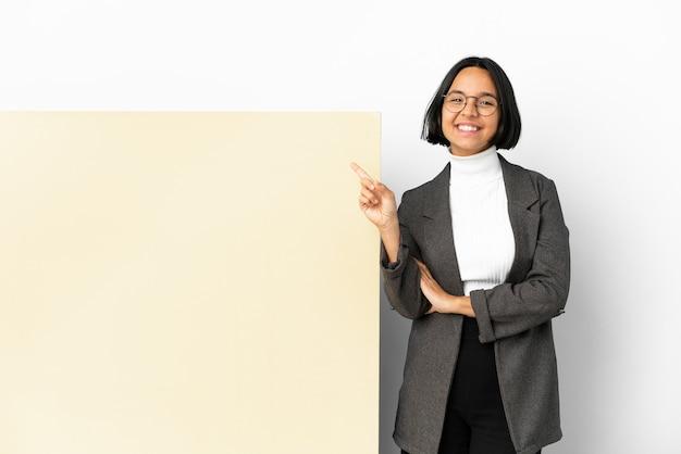 Młoda biznesowa kobieta rasy mieszanej z dużym banerem na białym tle szczęśliwa i skierowana w górę