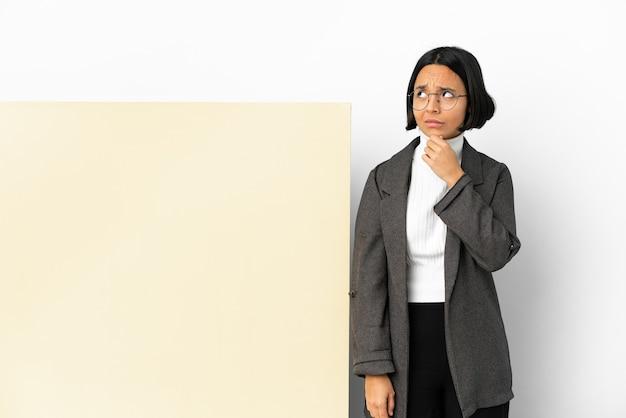 Młoda biznesowa kobieta rasy mieszanej z dużym sztandarem na białym tle ma wątpliwości