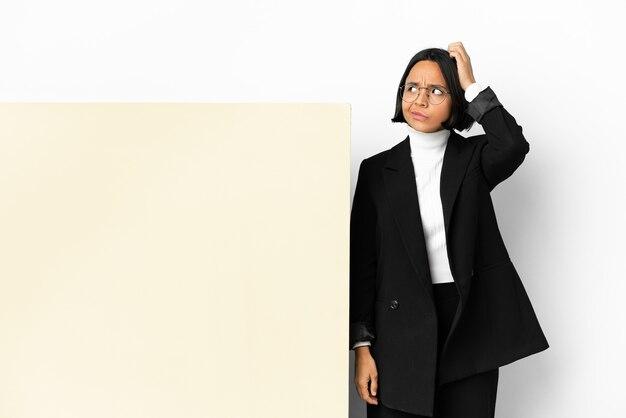 Młoda biznesowa kobieta rasy mieszanej z dużym sztandarem na białym tle, mając wątpliwości podczas drapania głowy