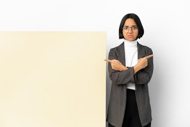 Młoda biznesowa kobieta rasy mieszanej z dużym sztandarem na białym tle, wskazując na boczne, które mają wątpliwości