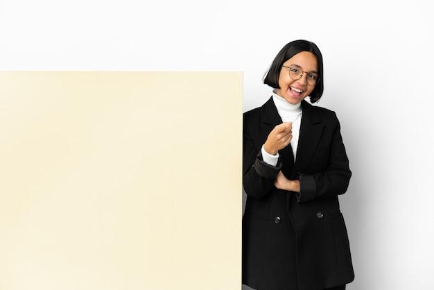 Młoda biznesowa kobieta rasy mieszanej z dużym sztandarem na białym tle zaskoczona i wskazująca przód
