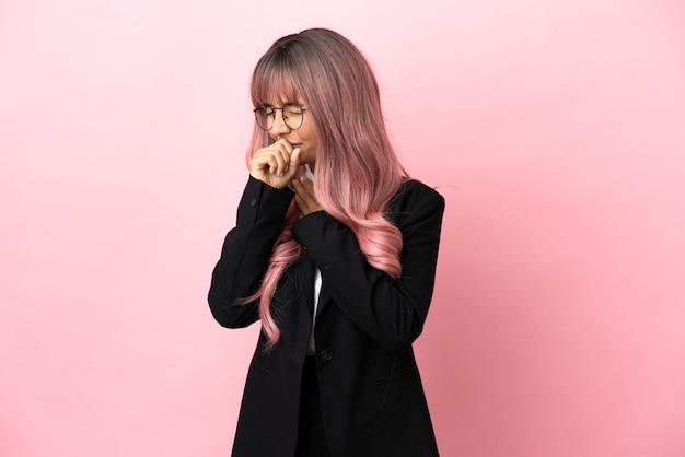 Młoda biznesowa kobieta rasy mieszanej z różowymi włosami na różowym tle cierpi na kaszel i źle się czuje
