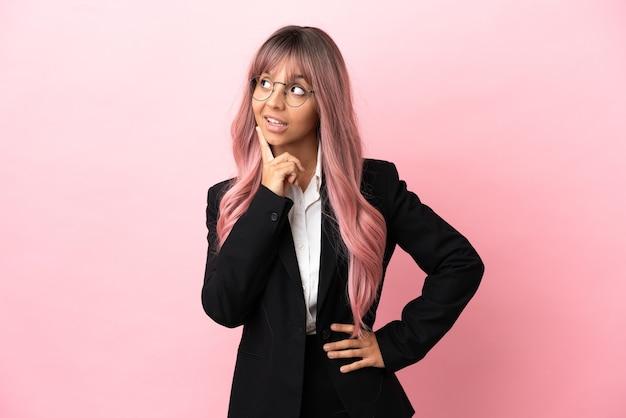 Młoda biznesowa kobieta rasy mieszanej z różowymi włosami na różowym tle, myśląca o pomyśle, patrząc w górę