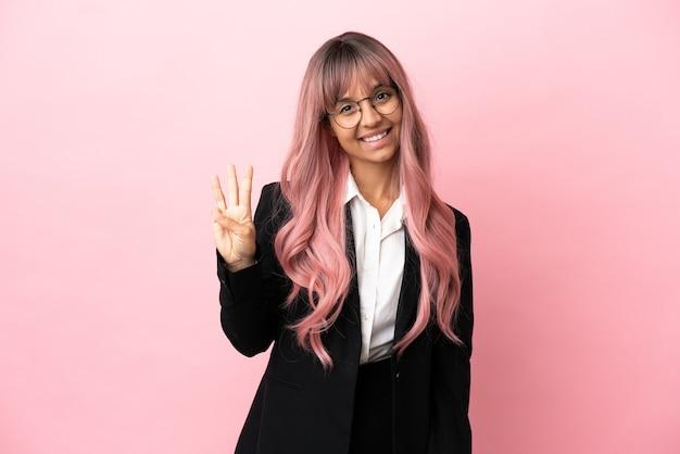 Młoda biznesowa kobieta rasy mieszanej z różowymi włosami na różowym tle szczęśliwa i licząca trzy palcami