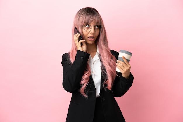 Młoda biznesowa kobieta rasy mieszanej z różowymi włosami na różowym tle, trzymająca kawę na wynos i telefon komórkowy