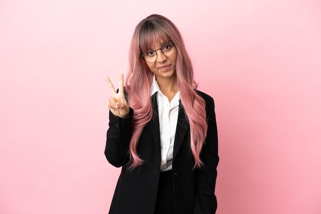 Młoda biznesowa kobieta rasy mieszanej z różowymi włosami na różowym tle, uśmiechnięta i pokazująca znak zwycięstwa