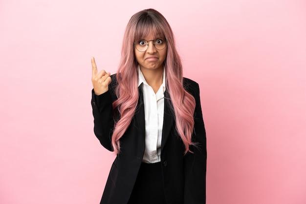 Młoda biznesowa kobieta rasy mieszanej z różowymi włosami na różowym tle, wskazując palcem wskazującym, to świetny pomysł