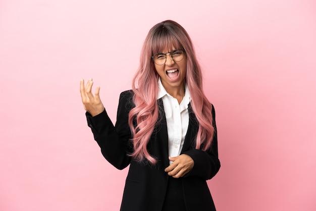 Młoda biznesowa kobieta rasy mieszanej z różowymi włosami na różowym tle, wykonując gest na gitarze