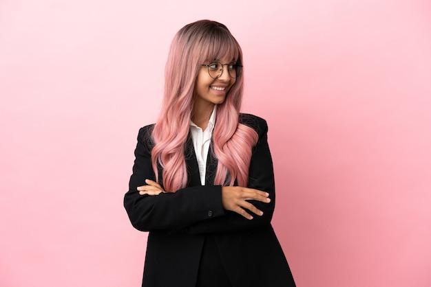 Młoda biznesowa kobieta rasy mieszanej z różowymi włosami na różowym tle ze skrzyżowanymi rękami i szczęśliwa