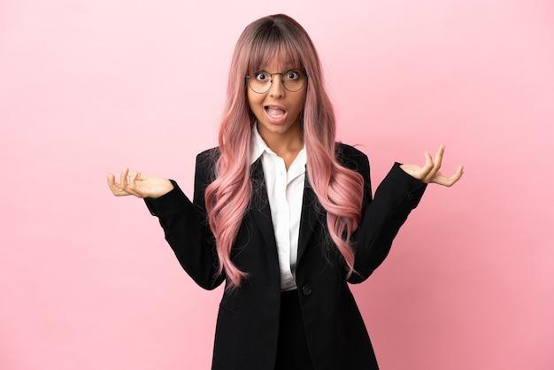 Młoda biznesowa kobieta rasy mieszanej z różowymi włosami na różowym tle ze zszokowanym wyrazem twarzy