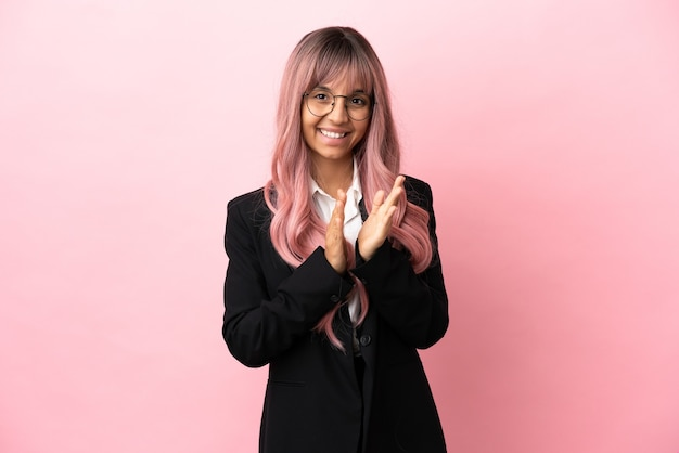 Młoda biznesowa kobieta rasy mieszanej z różowymi włosami odizolowana na różowym tle brawo po prezentacji na konferencji