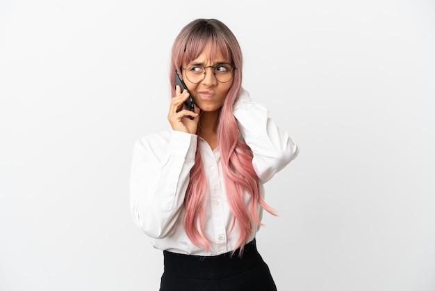 Młoda biznesowa kobieta rasy mieszanej z różowymi włosami, trzymająca telefon komórkowy na białym tle na różowym tle, mająca wątpliwości