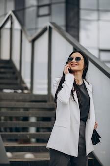 Młoda biznesowa kobieta rozmawia przez telefon na ulicy