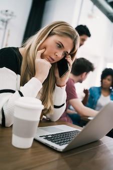 Młoda biznesowa kobieta rozmawia przez telefon