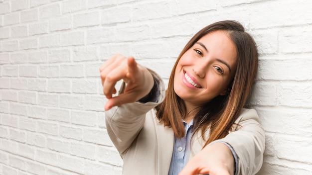 Młoda biznesowa kobieta rozochocona i uśmiechnięta wskazuje przód