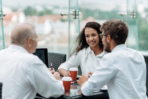 Młoda biznesowa kobieta ściska dłoń ze swoim partnerem biznesowym