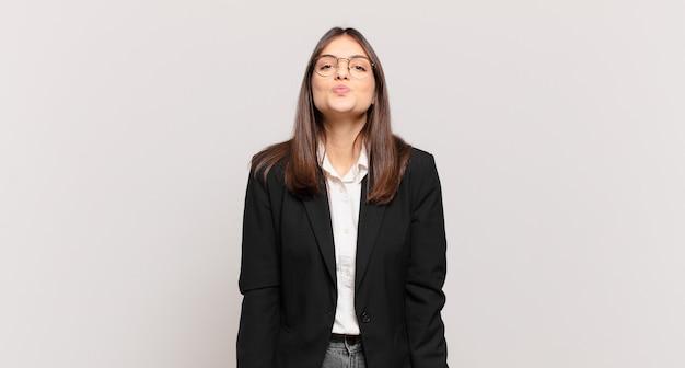 Młoda biznesowa kobieta ściska usta razem z uroczym, zabawnym, szczęśliwym, uroczym wyrazem twarzy, wysyłając buziaka